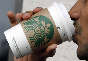 Photo - FILE - In this file photo taken July 26, 2011, a customer enjoys a coffee at Starbucks in Miami. It turns out Starbucks isn't contributing any upfront scholarship money to an online college degree program it introduced on Monday, June 16, 2014. (AP Photo/Alan Diaz, File)