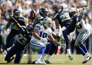 Photo -   Seattle Seahawks players break up a pass intended for Dallas Cowboys' Miles Austin, center, in the first half of an NFL football game on Sunday, Sept. 16, 2012, in Seattle. (AP Photo/Kevin P. Casey)