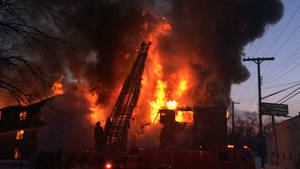 Photo - Firefighters battle a four-alarm fire at a three-story apartment complex Wednesday morning, March 5, 2014 on Detroit's west side. An official says the fire forced some people to jump to escape. (AP Photo/Detroit Free Press, Robert Allen)  DETROIT NEWS OUT;  NO SALES