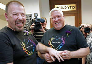 photo - Steven Bridges, left, receives a wedding ring from Michael Snell, early Saturday, Dec. 29, 2012, at City Hall in Portland, Maine. Same-sex couples in Maine are now legally allowed to marry under a new law that went into effect at 12:01 a.m. on Saturday. (AP Photo/Robert F. Bukaty)