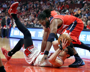 Photo - Chicago Bulls guard Kirk Hinrich scrambles for a loose ball with Washington Wizards forward Nene Hilario during Game 5 of an NBA basketball first-round playoff series, Tuesday, April 29, 2014, in Chicago. The Wizards won 75-69, taking the series. (AP Photo/Daily Herald, Steve Lundy) MANDATORY CREDIT  MAGS OUT