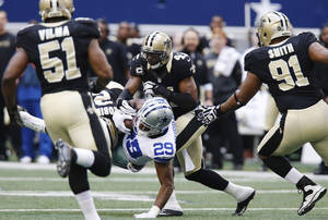Photo - Dallas Cowboys running back DeMarco Murray (29) is taken down by New Orleans Saints cornerback Patrick Robinson (21) and strong safety Roman Harper (41) as Saints' Will Smith (91) and Jonathan Vilma (51) move in during the second half of an NFL football game on Sunday, Dec. 23, 2012, in Arlington, Texas. (AP Photo/Sharon Ellman)  ORG XMIT: CBS128