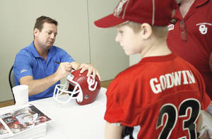 Photo - OU football coach Bob Stoops signs a helmet for Zac Godwin, 9, of Yukon, during the Sooner Caravan stop at the National Cowboy & Western History Museum on Thursday.  (Photo by Bryan Terry, The Oklahoman)