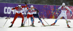 Photo - Switzerland's Dario Cologna, left, competes alongside Norway's Martin Johnsrud Sundby, Russia's Maxim Vylegzhanin and Sweden's Marcus Hellner, right, during the men's cross-country 30k skiathlon, at the 2014 Winter Olympics, Sunday, Feb. 9, 2014, in Krasnaya Polyana, Russia. Cologna got the gold, Hellner clinched the silver and  Sundby won the bronze medal. (AP Photo/Kirsty Wigglesworth)
