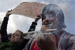 "Photo -   FILE - In this Friday April 20, 2012 file photo a man lights a large marijuana joint in Amsterdam during a protest against a government plan to stop foreigners from buying marijuana in the Netherlands. A Dutch judge has upheld the government's plan to introduce a ""weed pass"" on Friday, April 27, 2012, to prevent foreigners from buying marijuana in coffee shops. A lawyer for coffee shop owners says he will file an urgent appeal against Friday's ruling that clears the way for the introduction of the pass in southern provinces on May 1. (AP Photo/Peter Dejong, File)"