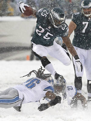 Photo - Philadelphia Eagles' LeSean McCoy (25) leaps over two would-be Detroit Lions tacklers as he runs to score his first of two touchdowns of an NFL football game on Sunday, Dec. 8, 2013, in Philadelphia. (AP Photo/Philadelphia Inquirer, Ron Cortes) PHILADELPHIA OUT; NEWARK, N.J. OUT; TV OUT; MAGAZINES OUT
