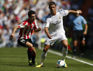 Photo - Real Madrid's Cristiano Ronaldo from Portugal, right steers the ball away from Athletic Bilbao's Iker Muniain during a Spanish La Liga soccer match at the Santiago Bernabeu stadium in Madrid, Spain Sunday Sept. 1, 2013. (AP Photo/Daniel Ochoa de Olza)