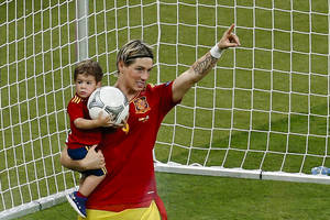 Photo -   Spain's Fernando Torres holds his son Leo after an award ceremony as Spain won the Euro 2012 soccer championship final between Spain and Italy in Kiev, Ukraine, early Monday, July 2, 2012. (AP Photo/Vadim Ghirda)