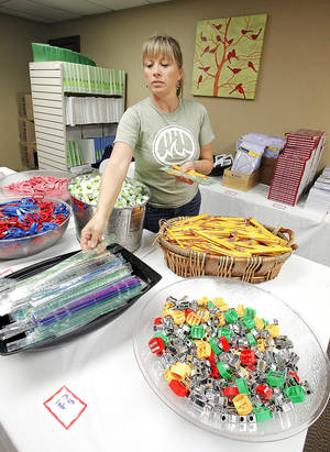 Photo - Leigh Scully, of Edmond, puts out school supplies for foster children to choose from at Citizens Caring for Children. PHOTOS BY PAUL B. SOUTHERLAND, The Oklahoman