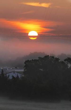 Photo - The sun rises over fog forming on the first day of August in northeast Oklahoma City Friday, Aug, 1, 2014. Photo by Paul B. Southerland, The Oklahoman