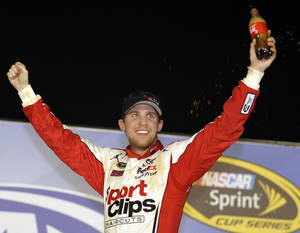 Photo -   Denny Hamlin celebrates in Victory Lane after winning the NASCAR Sprint Cup Series auto race at Atlanta Motor Speedway, Sunday, Sept. 2, 2012, in Hampton, Ga. (AP Photo/Rainier Ehrhardt)