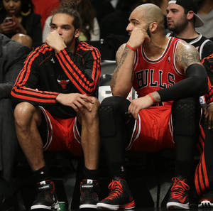 Photo - Chicago Bulls' Joakim Noah, left, and Carlos Boozer watch the end of the game against the Brooklyn Nets from the bench during the second half of Game 1 in the first round of the NBA basketball playoffs at the Barclays Center, Saturday, April 20, 2013, in New York. The Nets defeated the Bulls 106-89. (AP Photo/Seth Wenig)
