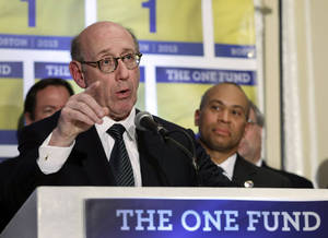 Photo - FILE - In this April 23, 2013 file photo, Kenneth Feinberg, an attorney who managed the 9/11 Victim Compensation Fund, speaks at a news conference in Boston as Massachusetts Gov. Deval Patrick, right, listens. The One Fund was established by Patrick and Boston Mayor Thomas Menino as a central place to gather donations for the Boston Marathon bombing victims. While giving is the reliable flip side to tragic events, charity watchdog groups recommend seeking out well-established charities or credibly backed efforts like The One Fund. (AP Photo/Elise Amendola, File)