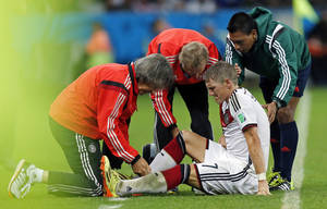 Photo - Germany's Bastian Schweinsteiger receives treatment during the World Cup round of 16 soccer match between Germany and Algeria at the Estadio Beira-Rio in Porto Alegre, Brazil, Monday, June 30, 2014. (AP Photo/Frank Augstein)