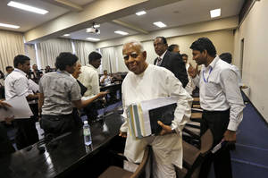 photo - Sri Lankan opposition lawmaker Rajavarothiam Sampanthan, foreground, leaves after addressing the media at the Parliament in Colombo, Sri Lanka, Friday, Dec. 7, 2012. Sri Lankan opposition lawmakers Friday withdrew from a committee looking into impeachment charges against Chief Justice Shirani Bandaranayake, saying the process is flawed and unfair. (AP Photo/Eranga Jayawardena)