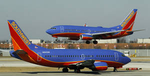 photo - FILE - In this Feb. 9, 2012 file photo, a Southwest Airlines Boeing 737 waits to take off at Chicago's Midway Airport as another lands. Southwest Airlines Co. says fourth-quarter earnings in 2012 fell by nearly half on higher spending for fuel, labor and maintenance. (AP Photo/Charles Rex Arbogast, File)