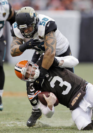 Photo - Cleveland Browns quarterback Brandon Weeden (3) is tackled by Jacksonville Jaguars defensive end Jason Babin (58) during the third quarter of an NFL football game on Sunday, Dec. 1, 2013, in Cleveland. (AP Photo/Tony Dejak)