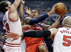 Photo - Washington Wizards guard Bradley Beal (3), center, drives to the basket against Chicago Bulls center Joakim Noah, left, and forward Carlos Boozer (5) during the first half in Game 1 of an opening-round NBA basketball playoff series in Chicago, Sunday, April 20, 2014. (AP Photo/Nam Y. Huh)