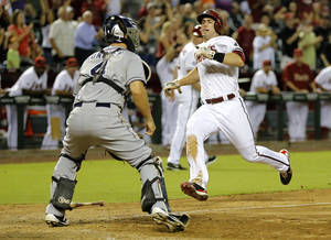 Photo - Arizona Diamondbacks' Paul Goldschmidt, right, scores on a two-run RBI double by teammate Martin Prado as San Diego Padres catcher Nick Hundley waits for the throw during the eighth inning of a baseball game, Tuesday, Aug. 27, 2013, in Phoenix. (AP Photo/Matt York)