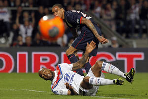 Photo - Lyon's Jimmy Briand, down, challenges for the ball with Paris Saint Germain's Gregory Van Der Wiel, up, during their French League One soccer match in Lyon, central France, Sunday, April 13, 2014. (AP Photo/Laurent Cipriani)