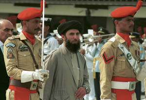 Photo - FILE - In this Wednesday, June 26, 1996 file photo, Gulbuddin  Hekmatyar, center, passes in front of an honor guard in the Afghan capital of Kabul, Afghanistan, after being sworn in as prime minister, ending four years of bitter fighting among U.S. backed rebels who took control of Kabul from the communist regime. Hekmatyar today is a U.S.-declared terrorist in hiding fighting international forces in Afghanistan. His representatives have opened talks with President Hamid Karzai's political opponents, as well as Karzai. (AP Photo, File)
