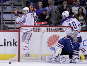 Photo - Edmonton Oilers left wing Taylor Hall raises his arms after scoring a goal against Colorado Avalanche goalie Semyon Varlamov (1) in the first period of an NHL game on Friday, April 19, 2013, in Denver. Oilers center Shawn Horcoff (10) skates to Hall. (AP Photo/Joe Mahoney)