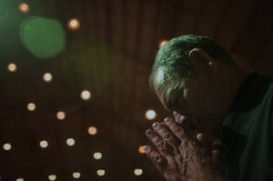Photo - A man prays during a Sunday mass at the Mother of God sanctuary in Sao Paulo, Brazil, Sunday March 3, 2013.  Catholics around the world attended the first Sunday masses since Benedict XVI stepped down as pope. Many prayed for a energetic, new leader to reinvigorate what many said was an ailing institution.(AP Photo/Andre Penner)