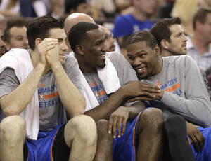 Photo - The Thunder's Nick Collison, left, Kendrick Perkins, center and Kevin Durant relax on the bench during the closing moments of Oklahoma City's 107-92 win over Sacramento late Tuesday night in Sacramento, Calif. Wednesday's Thunder-Clippers game finished after press time for this edition.                    AP photo