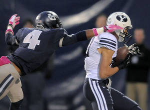 Photo - Brigham Young wide receiver Mitch Mathews catches a touchdown pass as Utah State's Tay Glover-Wright (4) defends during and NCAA football game on Friday, Oct. 4, 2013, in Logan, Utah. (AP Photo/The Herald Journal, Eli Lucero)