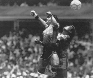 Photo - FILE - In this June 22, 1986 file photo  Argentina's Diego Maradona, left, beats England goalkeeper Peter Shilton to a high ball and scores his first of two goals in a World Cup quarterfinal soccer match, in Mexico City. Argentina's Diego Maradona was a football genius and is considered the closest challenger to Pele for the world's best ever player. But he is maybe most famous for cheating and getting away with it in the 1986 World Cup quarterfinals in Mexico when he jumped and punched the ball into England's net to give Argentina a 1-0 lead. To the fury of England's defenders and goalkeeper Peter Shilton, Tunisian referee Ali Bin Nasser awarded the goal. (AP Photo/El Grafico, Buenos Aires, File)