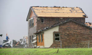 Photo - A house was damaged on the north side of State Highway 3 that was on the edge of a tornado moving north toward Piedmont.  Photo by Paul B. Southerland, The Oklahoman