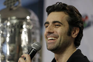 Photo - FILE - In this Dec. 19, 2013 file photo, Dario Franchitti, of Scotland, answers a question during  his first public appearance since a crash ended his IndyCar career during a press conference in Indianapolis. The three-time Indy 500 winner scoots through the Indianapolis Speedway paddock in a golf cart. Aside from a team meeting here or there, he marches to a wide-open schedule. Retirement suits the Scotsman well.  (AP Photo/Michael Conroy, File)