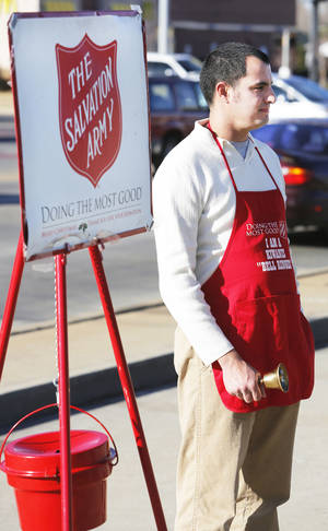 Photo - Salvation Army volunteer Adam Bush rings a bell while taking donations outside Byron's Liquor Store in Oklahoma City, Tuesday December 18, 2012. Photo By Steve Gooch, The Oklahoman