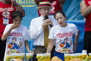 Photo - Sonya Thomas, right, reacts after winning the Nathan's Famous Fourth of July International Hot Dog Eating contest with 36 3/4 hot dogs and buns at Coney Island. AP Photos