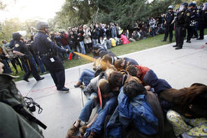 photo -   FILE - In this Nov. 18, 2011 file photo, University of California, Davis Police Lt. John Pike uses pepper spray to move Occupy UC Davis protesters while blocking their exit from the school&#039;s quad in Davis, Calif. The University of California plans to publish a long-awaited report on the pepper-spraying of student demonstrators by UC Davis police last fall online at noon Wednesday, April 11, 2012 a day after an Alameda County judge approved its publication without the names of most officers involved in the Nov. 18 clash. (AP Photo/The Enterprise, Wayne Tilcock, File)  