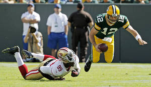 Photo -   San Francisco 49ers' Aldon Smith (99) sacks Green Bay Packers' Aaron Rodgers (12) during the first half of an NFL football game Sunday, Sept. 9, 2012, in Green Bay, Wis. (AP Photo/Mike Roemer)