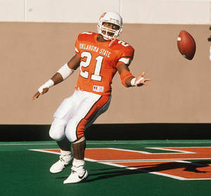 Photo - OKLAHOMA STATE UNIVERSITY / COWBOYS FOOTBALL:  OSU running back Barry Sanders tosses the ball after his NCAA- record setting 30th touchdown. BY PAUL HELLSTERN.