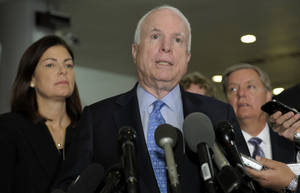 Photo - Sen. John McCain, R-Ariz., ranking Republican on the Senate Armed Services Committee, center, flanked by fellow committee members, Sen. Kelly Ayotte, R-N.H., left, and Sen. Lindsey Graham, R-S.C., right, speaks  on Capitol Hill in Washington, Tuesday, Nov. 27, 2012, following a meeting with UN Ambassador Susan Rice. Rice met with lawmakers to discuss statements she made about the attack on the U.S. Consulate in Libya that left the ambassador and three other Americans dead. (AP Photo/Susan Walsh)