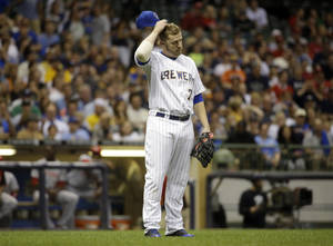 Photo - Milwaukee Brewers first baseman Mark Reynolds reacts after a throwing error during the fifth inning of a baseball game against the Cincinnati Reds Friday, June 13, 2014, in Milwaukee. (AP Photo/Morry Gash)