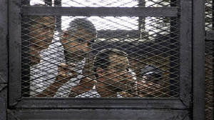Photo - From left, Australian correspondent Peter Greste, Canadian-Egyptian acting bureau chief of Al-Jazeera Mohamed Fahmy, and Egyptian producer Baher Mohammed, appear in a defendant's cage in a courtroom in Cairo, Egypt, Monday, June 23, 2014. An Egyptian court on Monday convicted three journalists from Al-Jazeera English and sentenced them to seven years in prison each on terrorism-related charges, bringing widespread criticism that the verdict was a blow to freedom of expression. The three, Greste, Fahmy and Mohammed, have been detained since December charged with supporting the Muslim Brotherhood, which has been declared a terrorist organization, and of fabricating footage to undermine Egypt's national security and make it appear the country was facing civil war. (AP Photo/Heba Elkholy, El Shorouk Newspaper) EGYPT OUT
