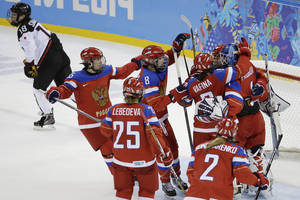 Photo - Team Russia celebrates their 2-1 win over Japan as Tomoko Sakagami of Japan skates past after the 2014 Winter Olympics women's ice hockey game at Shayba Arena, Tuesday, Feb. 11, 2014, in Sochi, Russia. (AP Photo/Mark Humphrey)