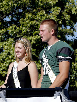 Photo - Homecoming court members Sydney Graham and Justice Hansen ride in a float during the Edmond Santa Fe homecoming parade. PHOTO BY SARAH PHIPPS, THE OKLAHOMAN <strong>SARAH PHIPPS - THE OKLAHOMA</strong>