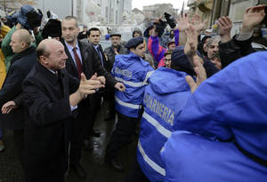 Photo - Romania's President Traian Basescu, left, speaks to supporters gathered outside a voting station in Bucharest, Romania, Sunday, Dec. 9, 2012. Millions of Romanians braved rain and snow Sunday as they went to the polls for a parliamentary election that center-left government is expected to win a, but the result could lead to more of the political instability that has plagued the impoverished Balkan nation this year. (AP Photo)