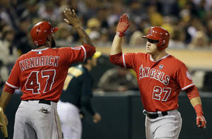 Photo - Los Angeles Angels' Mike Trout, right, is congratulated by Howie Kendrick (47) after Trout scored against the Oakland Athletics in the fifth inning of a baseball game, Monday, Sept. 16, 2013, in Oakland, Calif. (AP Photo/Ben Margot)