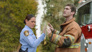 """Photo - This publicity image released by CBS shows Natalie Martinez, left, and her Josh Carter in a scene from the series """"Under the Dome,"""" about a small town that is suddenly and inexplicably sealed off from the rest of the world by a massive transparent dome. The Nielsen company says an estimated 13.5 million people watched the debut last week. More than 3 million watched on their DVRs or through on-demand services, and CBS reran the premiere Sunday, which drew another 5.1 million viewers. A second episode that ran Monday was seen by 11.5 million people. (AP Photo/CBS Entertainment) ORG XMIT: NYET540"""
