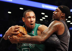 Photo - Boston Celtics forward Jared Sullinger (7) and Brooklyn Nets forward-center Andray Blatche (0) battle for the ball in the first half of their NBA basketball game at the Barclays Center, Tuesday, Dec. 25, 2012, in New York. (AP Photo/John Minchillo)