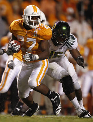 Photo -   FILE - This Sept. 11, 2010 file photo shows Tennessee running back David Oku (27) carrying the ball as he's hit by Oregon linebacker Michael Clay (46) during an NCAA football game at Neyland Stadium in Knoxville, Tenn. Oku has signed with Arkansas State. ASU coach Gus Malzahn announced the signing of the former standout from Midwest City, Okla., on Wednesday, June 27, 2012. (AP Photo/Wade Payne, File)