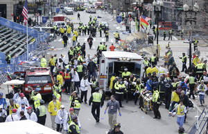Photo - Medical workers aid injured people at the finish line of the 2013 Boston Marathon following an explosion in Boston, Monday, April 15, 2013. (AP Photo/Charles Krupa) ORG XMIT: MACK120