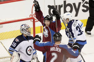 Photo - Colorado Avalanche's Matt Duchene, top, celebrates after scoring the game winning goal past Winnipeg Jets goalie Al Montoya (35) during overtime of an NHL hockey game on Monday, March 10, 2014 in Denver. The Avalanche won 3-2. (AP Photo/Barry Gutierrez)