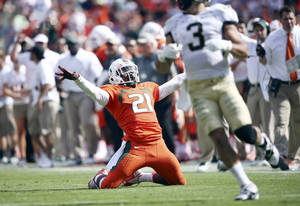 Photo - Miami's Antonio Crawford (21) celebrates after breaking up a pass for Wake Forest's Michael Campanaro (3) during the second half of an NCAA college football game in Miami Gardens, Fla., Saturday, Oct. 26, 2013. Miami won 24-21. (AP Photo/J Pat Carter)